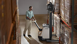Man with crown pallet jack and crown electric pallet jack